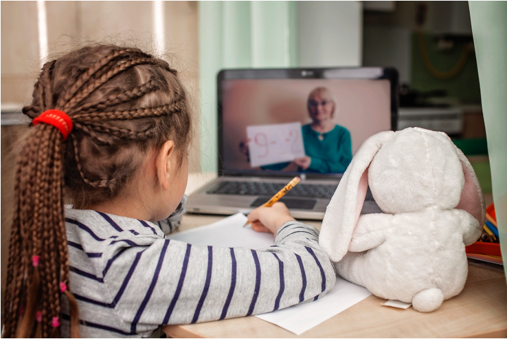 Photo of a student learning virtually. Her teacher can be seen on the computer screen holding a math problem. The student is holding her pencil over a worksheet and has her stuffed bunny sitting on the table next to her.