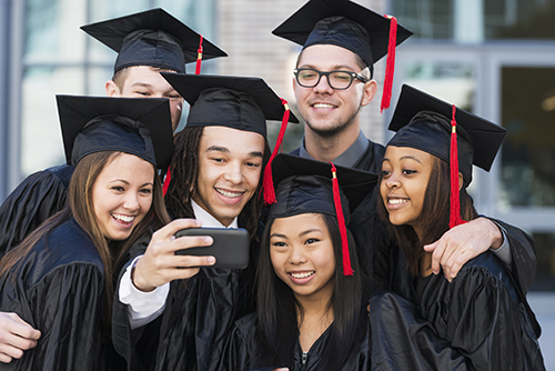 Multiracial group of six friends taking a selfie at graduation, in their black caps and gowns.